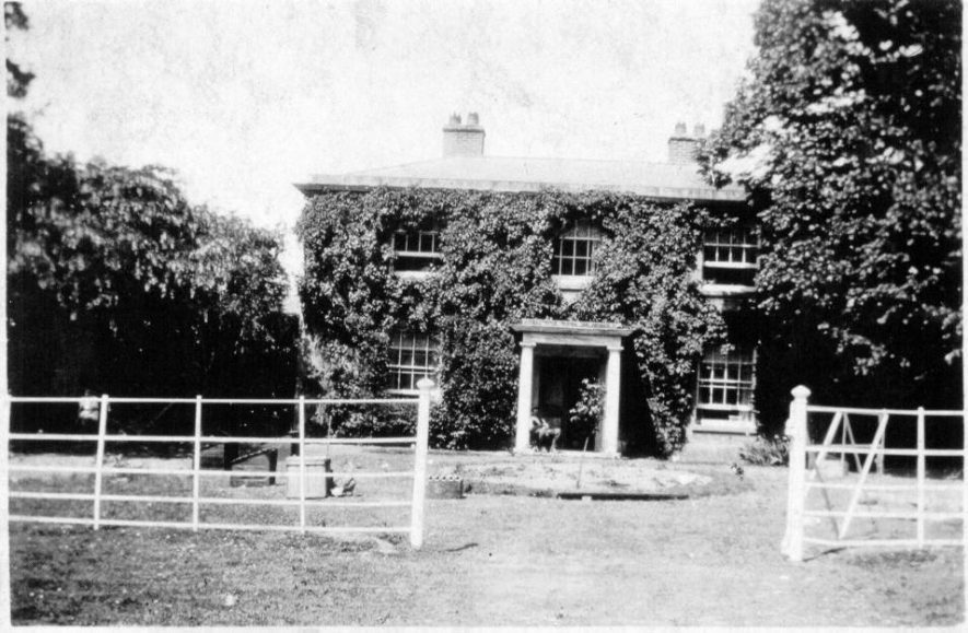 Black and white photo of an ivy covered two storey house with white fence in front | Image supplied by John Finnemore, given to him by previous owners of Haselor Lodge