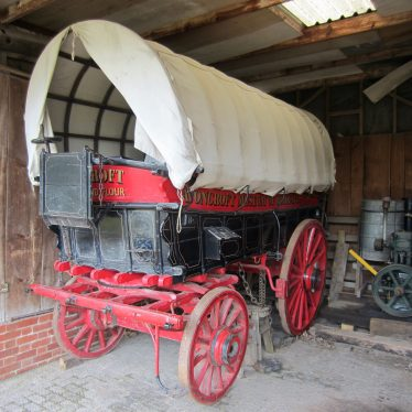 Red and black painted wagon with cloth covering | Image courtesy of Anne Langley