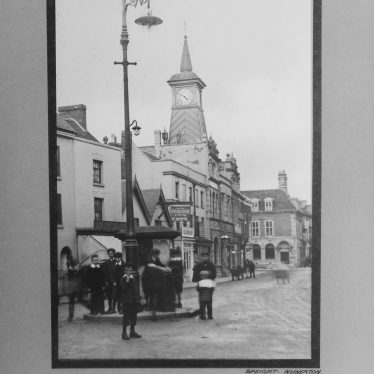 Photograph of Nuneaton: 'Milby', George Eliot postcard series. Street scene showing the Peacock Inn and Market Place Clock Tower (including traffic island). | Photographer Clare Speight, Warwickshire County Record Office reference CR4781/156