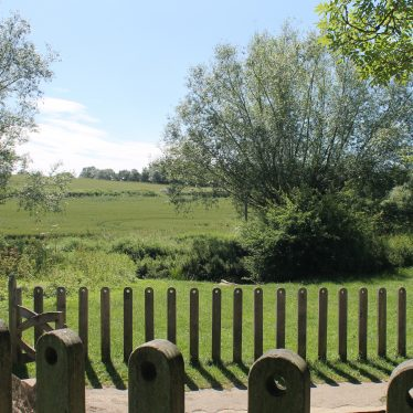 A view across fields with part of the well in the foreground | Image courtesy of L Caves