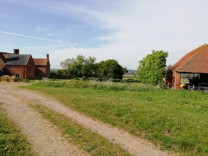 Country track cutting diagonally up photo right to left, with redbrick buildings surrounded by trees in background   Image courtesy of Gary Stocker May 2020