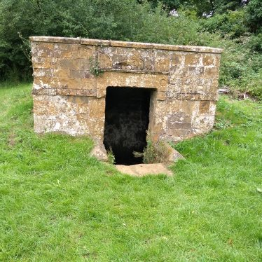Old well surround looks like a stone fireplace on a small grassy mount | Image courtesy of Graham Clutton