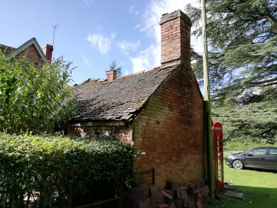 Back and side view of a redbrick house with tall chimney with hedge in front | Image courtesy of Gary Stocker August 2020.