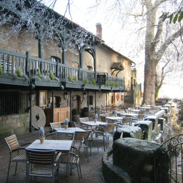 Stone building with wooden balcony, millstone, tables & chairs outside | Image courtesy of Anne Langley