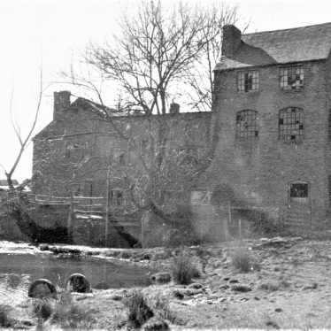Black and white photo of Ragley Needle Mill showing the mill buildings and tail race | June Booth