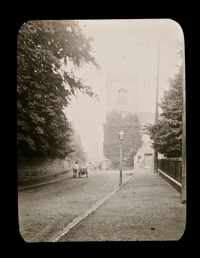 Church tower and man with hand-cart in street with wide pavement and trees | Courtesy of Warwickshire CC, Rugby Library Local Studies Collection. Warwickshire County Record Office reference PH 827/5/48, photographer Rev E.N.Dew