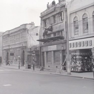 Photograph of demolition work on Lesters (Chemist) shop (centre, left), and the 'White Swan' pub (centre, right) in the Market Place. 6th December 1964. | Warwickshire County Record Office reference PH882/3/1964