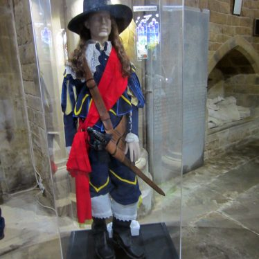 Gentleman with red sash, sword, blue suit and large black hat | Image courtesy of Anne Langley