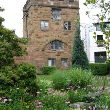 Red sandstone tower with battlements and windows with garden in front | Image courtesy of Anne Langley