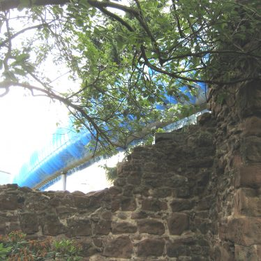 Low section of red sandstone wall with modern building behind   Image courtesy of Anne Langley