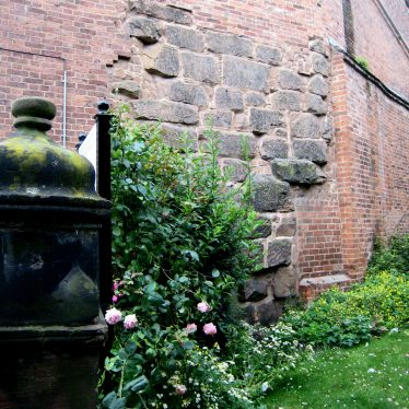 Blocks of red sandstone incorporated in a tall brick building, garden in front   Image courtesy of Anne Langley