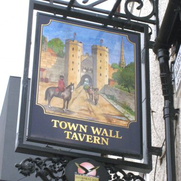 Pub sign with picture of town gate with twin towers, horseman outside and church spire inside | Image courtesy of Anne Langley