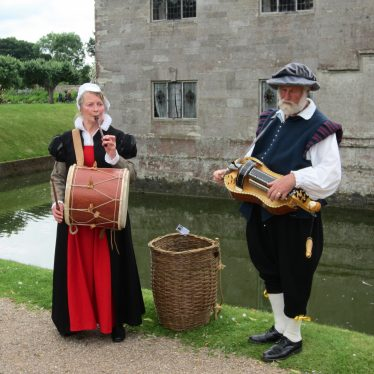 Woman and man in tudor costume with moat and stone manor house behind | Image courtesy of Anne Langley