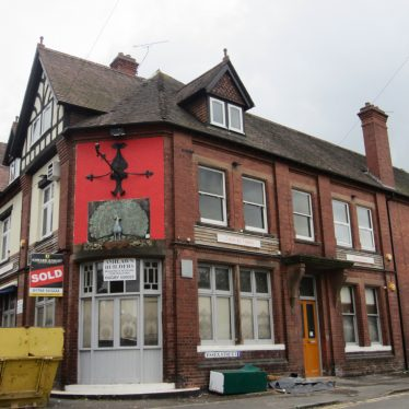 Red brick 2-storey corner building with dormer windows in the tiled roof. Red painted end wall with pub and 'SOLD' signs | Anne Langley