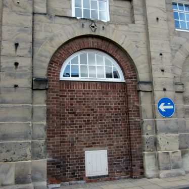 Bricked up archway in stone building with dark markings either side and above | Image courtesy of Anne Langley