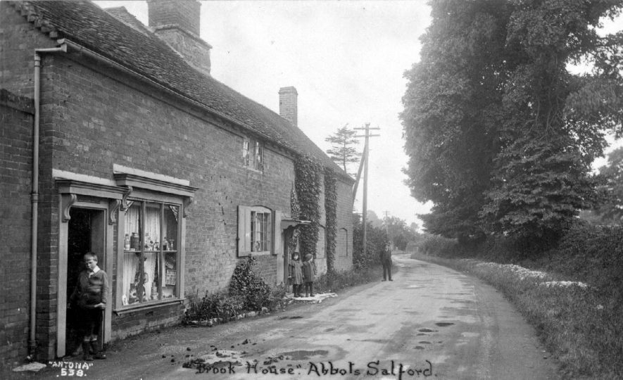 Cottages in Abbots Salford, the nearest one appears to be a local shop. 1920s. The road is a dirt track and banks round to the left, the cottages are on the left hand side, with trees on the right. | Warwickshire County Record Office reference PH350/1938