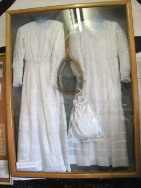 Tennis memorabilia from Maud Watson, 1884 Wimbledon champion. Two white dressed with long sleeves, a wooden tennis raquet and a white bag | Image courtesy of Anne Langley