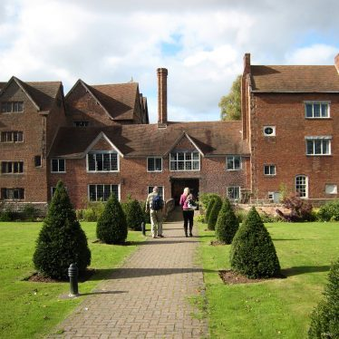Red brick building with central two-storey link between two taller parts (4 stories tall); garden with clipped yews in front | Anne Langley