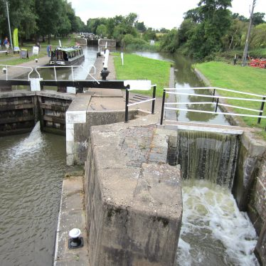 Two locks side by side; narrow boat using wider one; canal basin and flight of locks in distance | Anne Langley