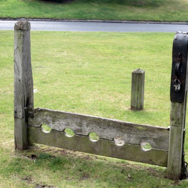 Wooden stocks with five holes on green | Image courtesy of Anne Langley