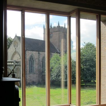 Church of red sandstone with tower seen through large picture window | Image courtesy of Anne Langley
