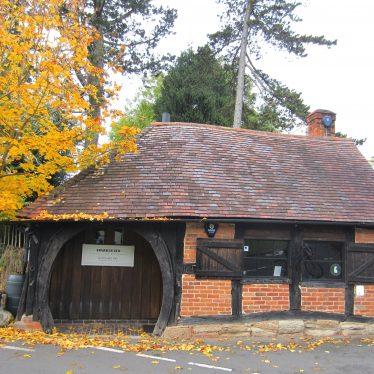 One-storey timber-framed and red brick building with horseshoe doorway and tiled roof; autumn leaves on tree beside | Image courtesy of Anne Langley