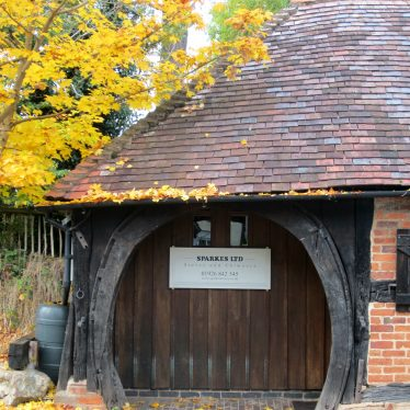 Large wooden horseshoe archway in one-storey timber-framed & red brick building with tiled roof, autumn leaves on tree beside | Image courtesy of Anne Langley