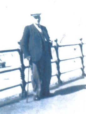 Robert Oakley. he has a stick by his side, and is leaning against an iron rail   Image courtesy of Iris Painter