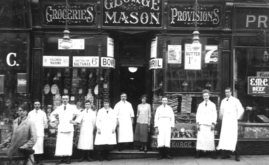 George Mason  (grocers) 68, The Parade, Leamington Spa,  with the staff assembled outside.  1920s  [It has been suggested that the gentleman beneath the'AS' of MASON is the manager Albert Edward Mason (not related to the owner) and that the photo was taken after August 1924.] |  IMAGE LOCATION: (Warwickshire County Record Office)