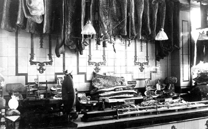 Interior of George Masons shop at 38, The Parade Leamington Spa, showing the smoked bacon department  with a hand bacon slicer.  1920s |  IMAGE LOCATION: (Warwickshire County Record Office)