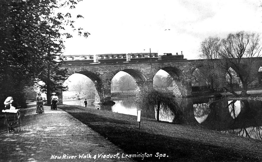 The railway viaduct over the River Leam, Victoria park, Leamington.   There are three ladies pushing their infants in perambulators along the river-side path.  A passenger train is crossing the bridge, a steam engine and three carriages.  1900s |  IMAGE LOCATION: (Warwickshire County Record Office)