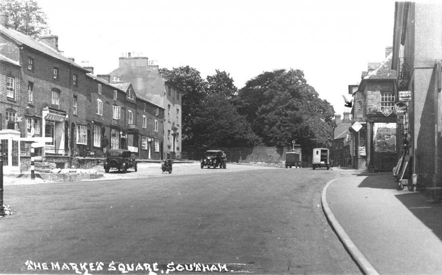 View north along Market Hill, showing the Craven Arms Hotel and shops; also cars, delivery vans and a motor bike.  1930s |  IMAGE LOCATION: (Warwickshire County Record Office)