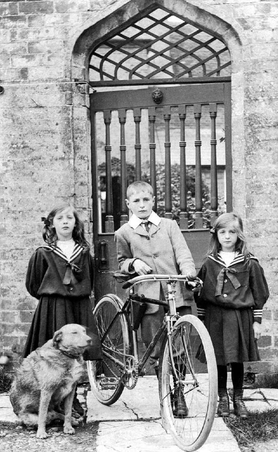 One boy with bicycle, two girls with sailor collars with their dog by ornate barred gateway, Leamington Spa.  1900s |  IMAGE LOCATION: (Warwickshire County Record Office)