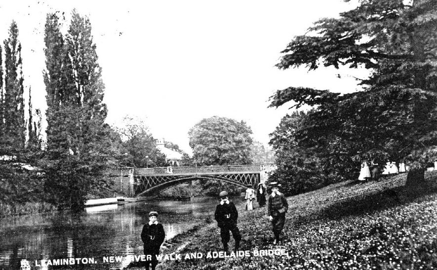 New river walk and Adelaide Bridge, Leamington Spa. Three boys on river bank, ladies in background.  1900s |  IMAGE LOCATION: (Warwickshire County Record Office)
