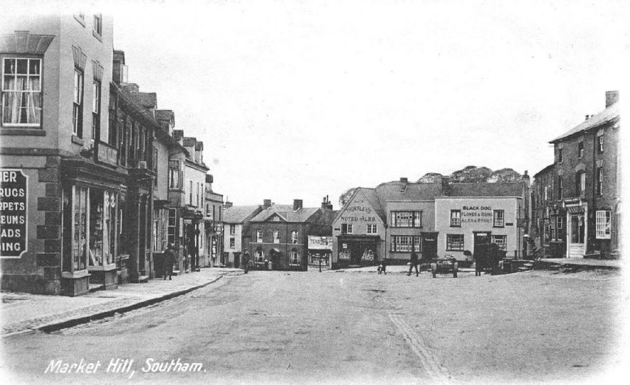 View looking south west down Market Hill, showing shops, and the Black Dog Inn; two cars parked outside the Inn.  c.1910 |  IMAGE LOCATION: (Warwickshire County Record Office)