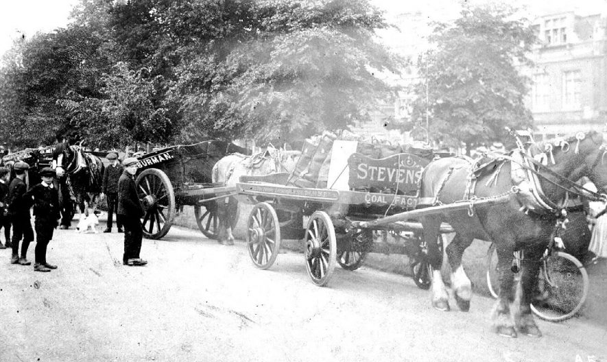 Leamington Spa. Cart Horse Parade, showing working cart horses, with carts, drays etc. Three boys watching.  1910s |  IMAGE LOCATION: (Warwickshire County Record Office)