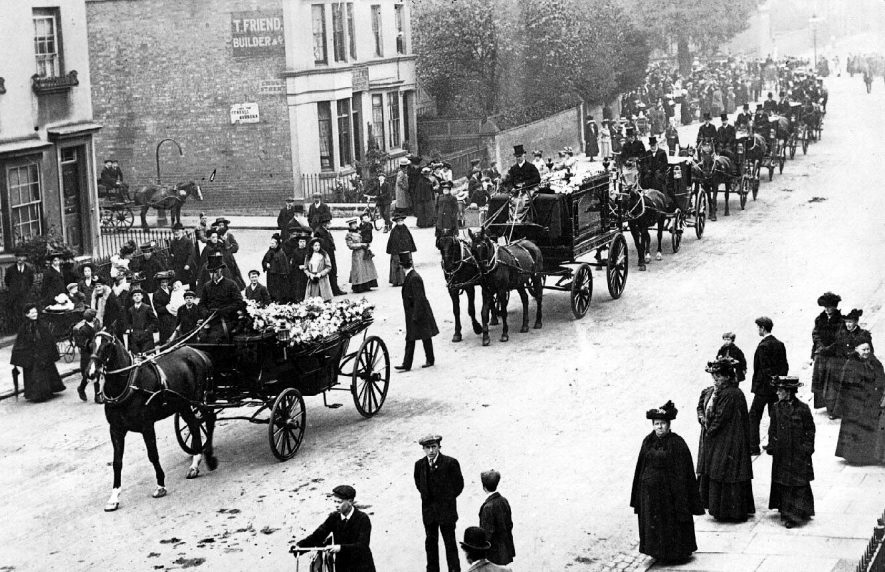 Clarendon Street, Leamington Spa.  Large funeral procession, showing  horsedrawn hearse and carriages, undertakers and drivers, onlookers. Sign on building: