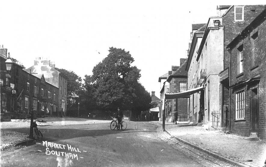View looking north east up Market Hill, showing shops; boy in uniform with bicycle standing in the road.  Postmark 1912 |  IMAGE LOCATION: (Warwickshire County Record Office)