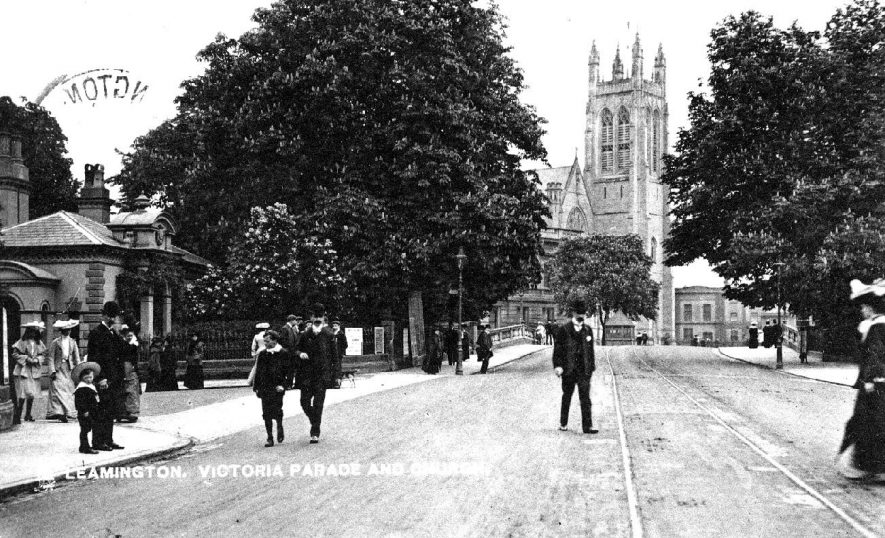 Victoria Parade with Parish Church and Lodge at entrance to Jephson Gardens. People walking in the road.  1900s |  IMAGE LOCATION: (Warwickshire County Record Office)