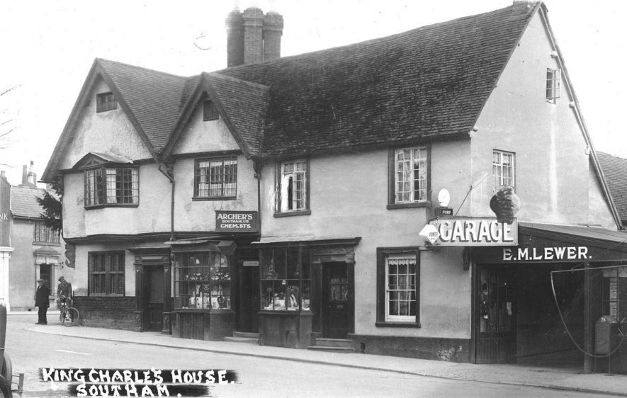 'King Charles House', Manor House, Market Hill, shows Archer's chemist shop and E.M. Lewer's garage; two men standing on the corner of the road, one with a bicycle.  Postmark 1933 |  IMAGE LOCATION: (Warwickshire County Record Office)