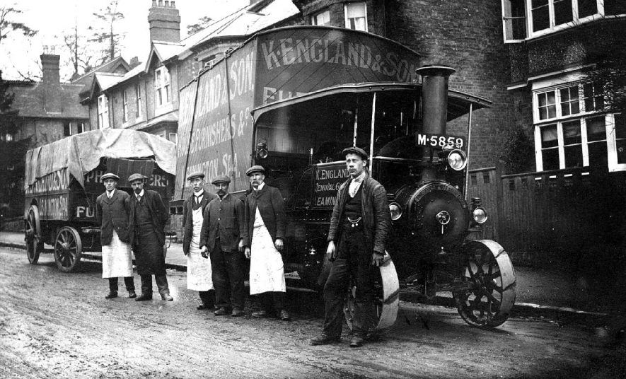 Steam engine and two  trailers, belonging to K England, house furnishers, Leamington Spa, standing in street. Driver and workers posing by engine.  1900s |  IMAGE LOCATION: (Warwickshire County Record Office)