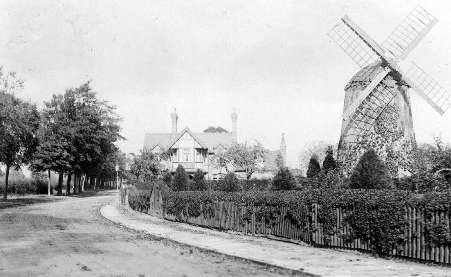 Windmill with sails but probably not in working use, surrounded by garden with suburban house next door, Tachbrook Road, Leamington Spa.  1900s