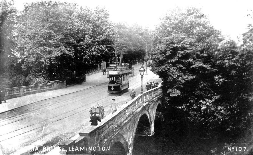 Victoria Bridge, Leamington Spa, with tram passing over. Road sweepers hand cart in foreground.  1900s |  IMAGE LOCATION: (Warwickshire County Record Office)