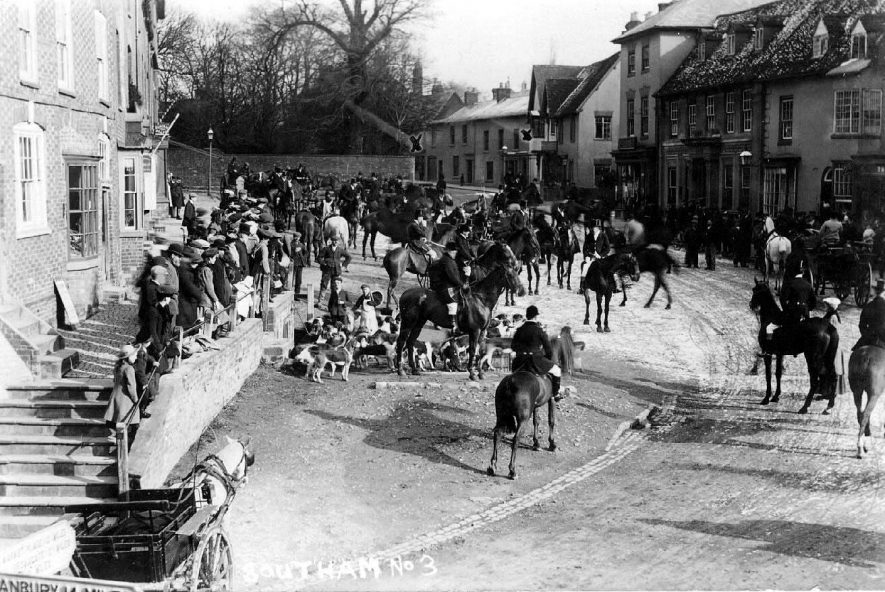 Hunt meet on the Market Hill; shows the huntsmen and hounds being watched by a small crowd, several horse drawn carriages are also in the photograph. Photo:  no.3.  Postmark 1907 |  IMAGE LOCATION: (Warwickshire County Record Office)