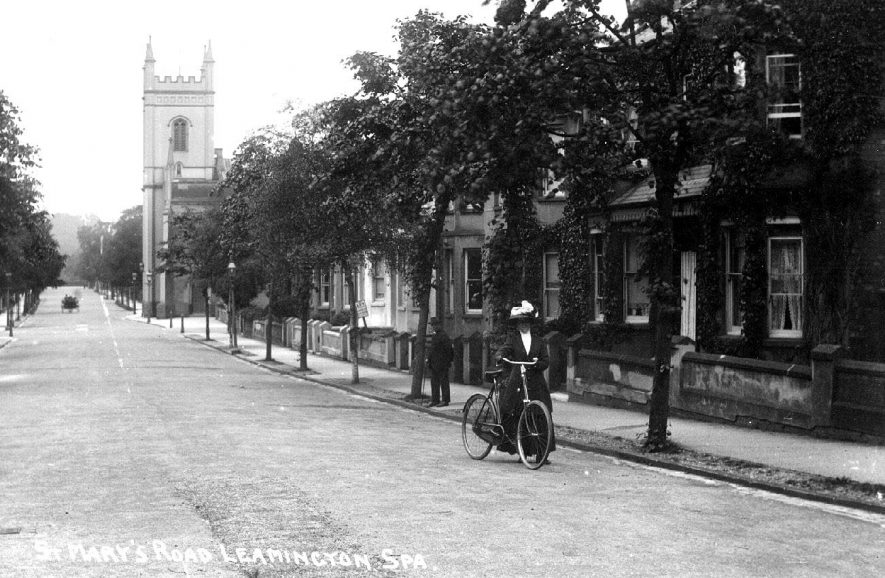 Lady pushing her bicycle along St Mary's Road. St Mary's church in the background.  1910s |  IMAGE LOCATION: (Warwickshire County Record Office)