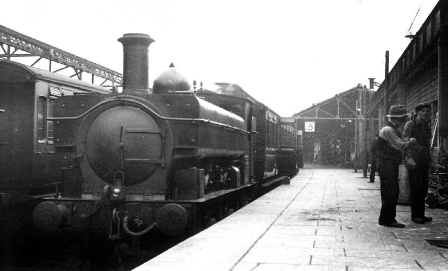 Leamington Spa Station during reconstruction. Railway platform and buildings. Steam engine and carriages. Two workmen.  1936 |  IMAGE LOCATION: (Warwickshire County Record Office)
