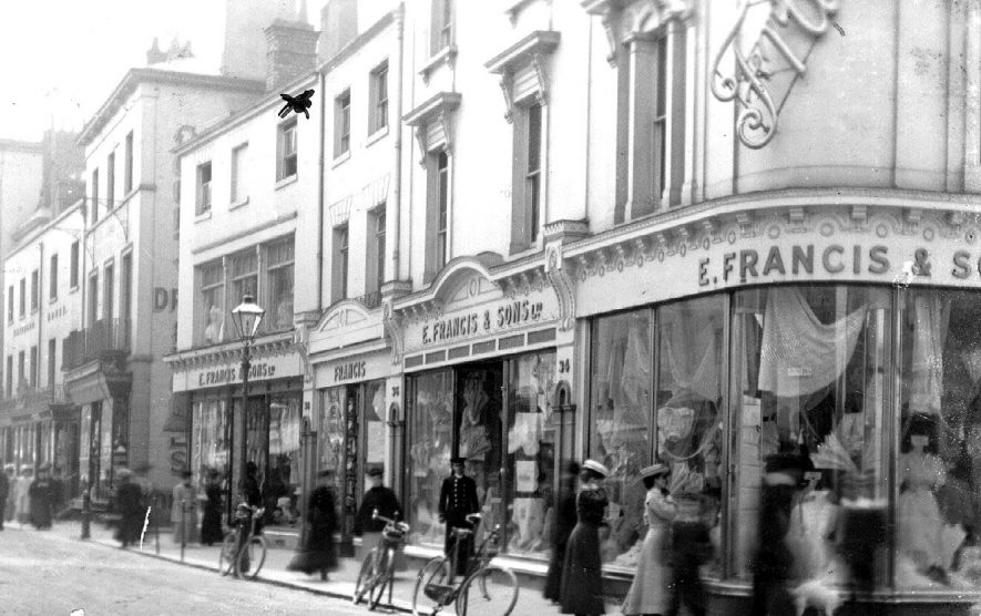 Shop front of E. Francis & Sons Ltd., drapers, Leamington Spa.  Ladies shopping. Doorman in uniform, gas street lamp.  1900s |  IMAGE LOCATION: (Warwickshire County Record Office)