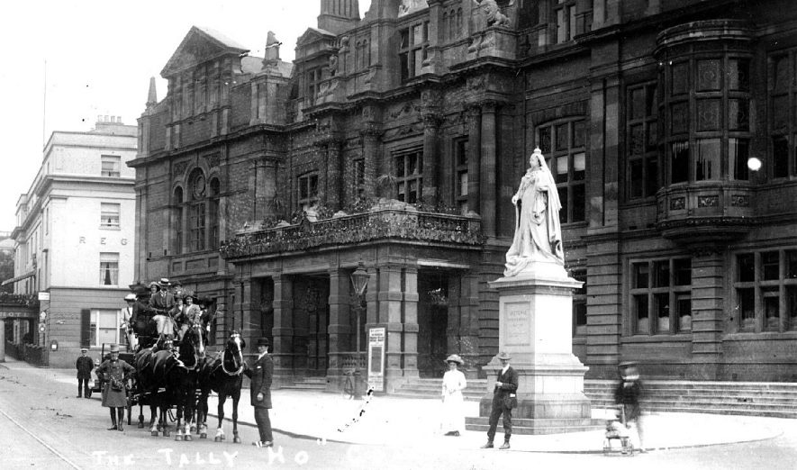 Leamington Spa Town Hall showing the statue of Queen Victoria and the Tally Ho Coach (Leamington Spa & Stratford upon Avon) standing in road passengers on board. Driver and on-lookers in street.  1900s |  IMAGE LOCATION: (Warwickshire County Record Office)