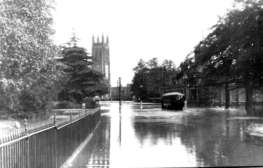 Lower Parade opposite the Pump Rooms under water.  All Saint's Church tower in distance. Street lamps.  Leamington Spa.  1920s |  IMAGE LOCATION: (Warwickshire County Record Office)