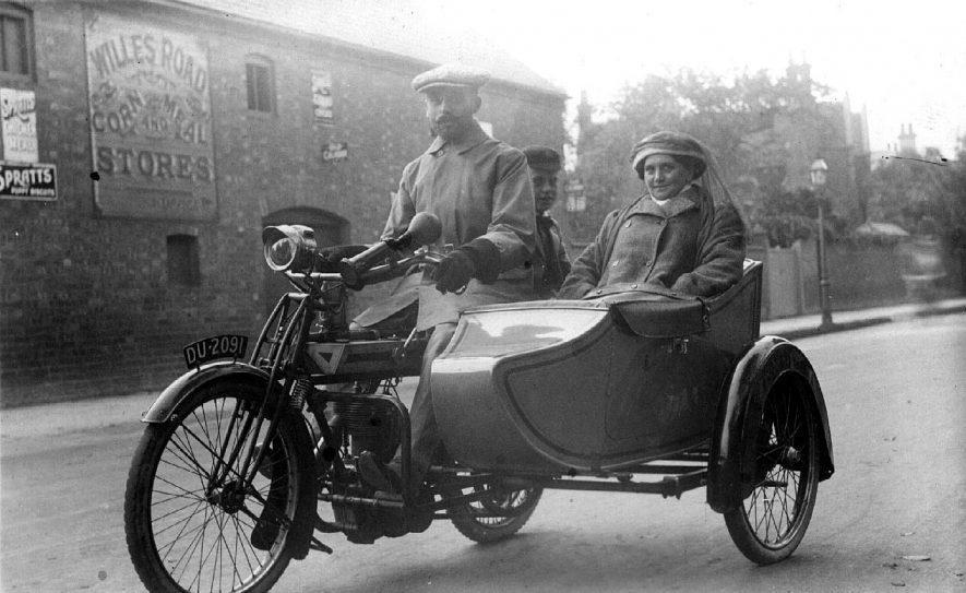 Motorcycle and sidecar with three passengers outside Willes Road corn store.  1900s |  IMAGE LOCATION: (Warwickshire County Record Office)